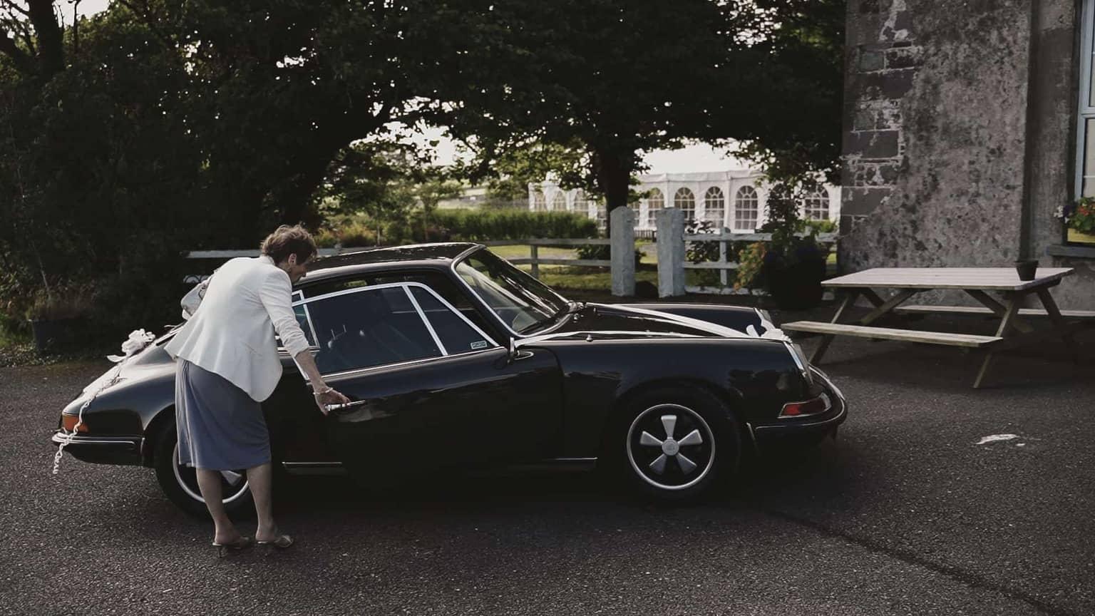 Grandmother is checking Porsche interior.