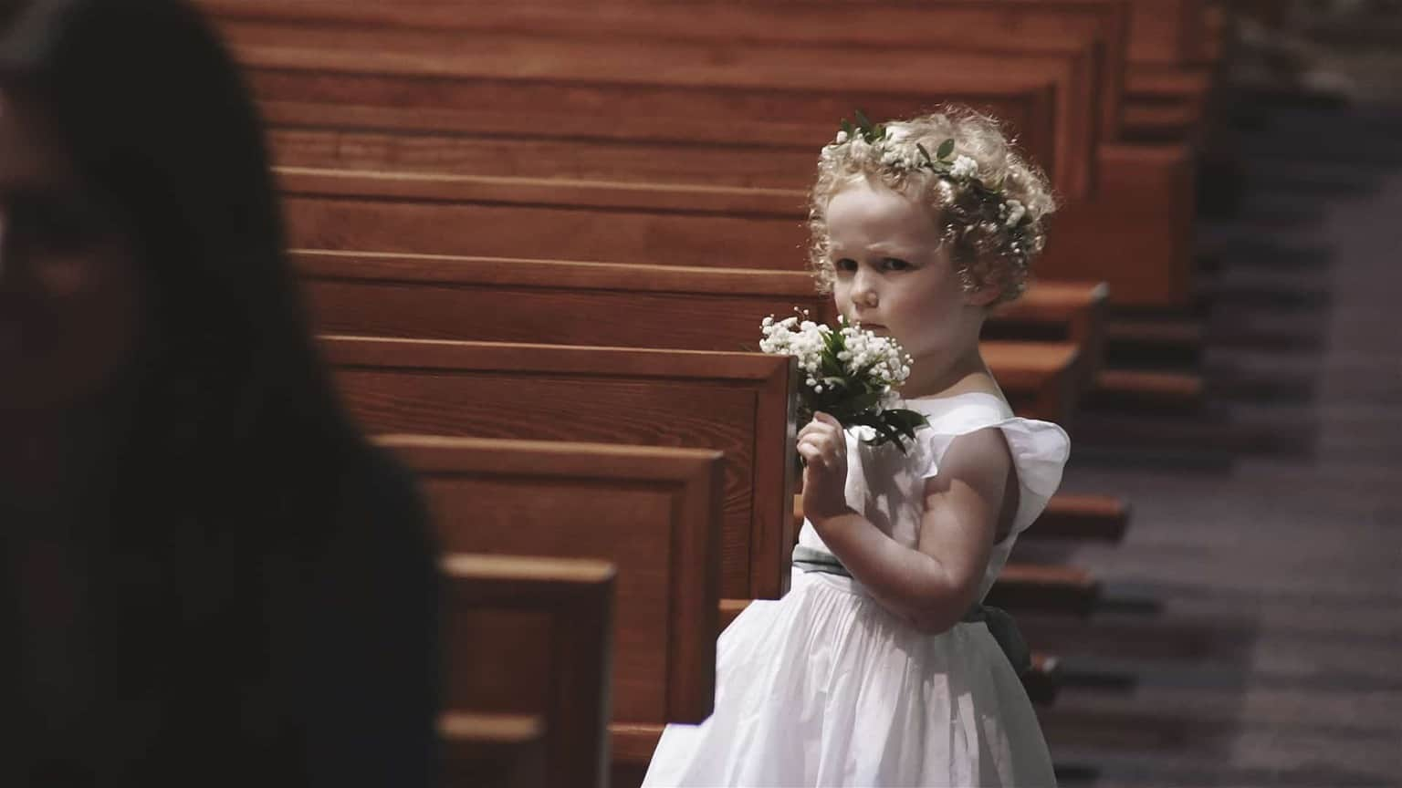 Flower girl looking ab sad and holding flowers