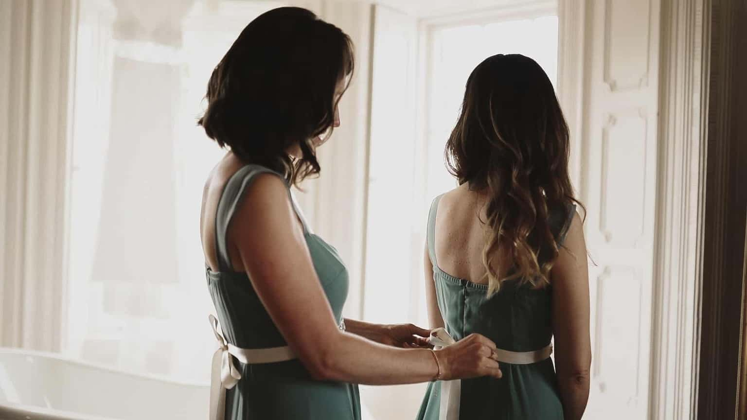 Bridesmaid getting dressed and tiding ribbons.