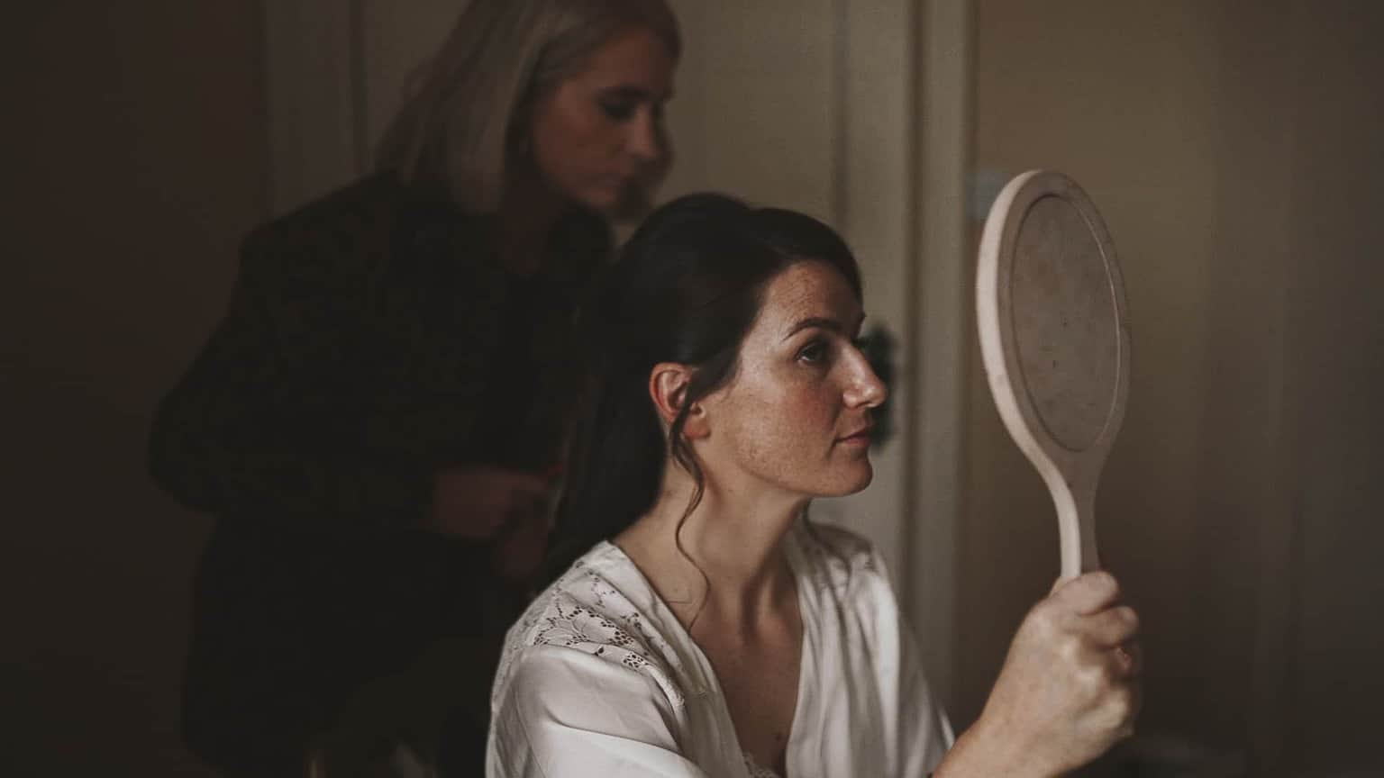 Bride finally looking at mirror and check in make up.