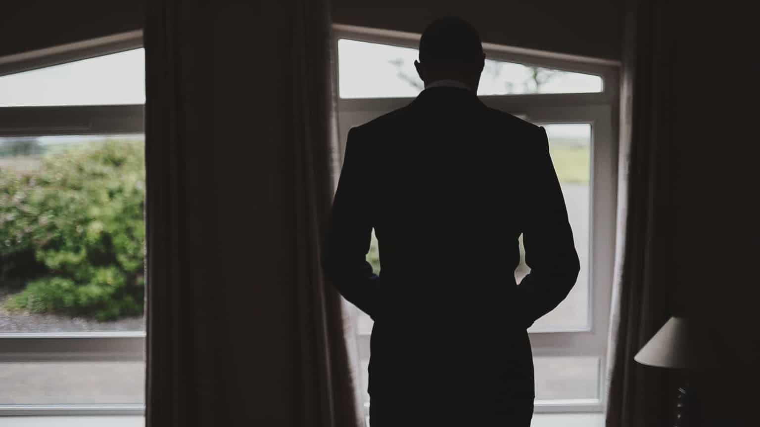Groom is putting suit and looking outside widow.