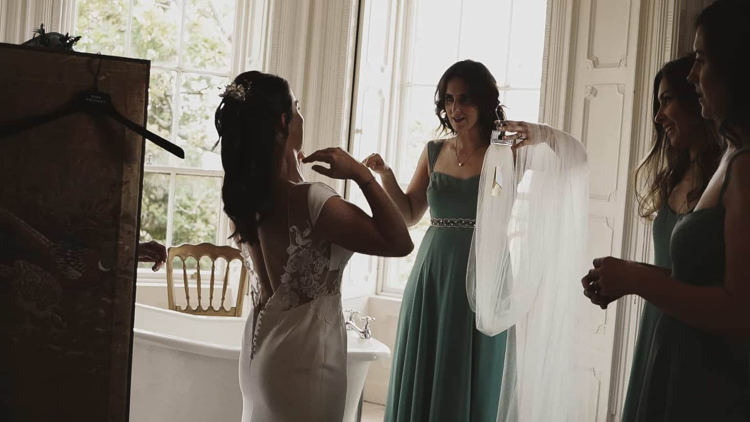 Bride is getting dress, one of bridesmaid is holding veil.