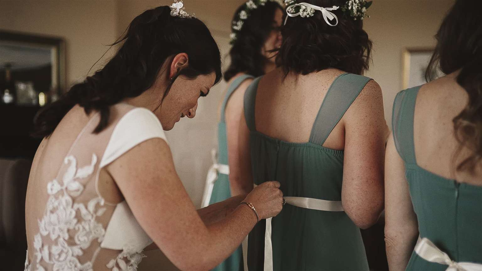 Bride is helping to tide ribbons on bridesmaid dresses