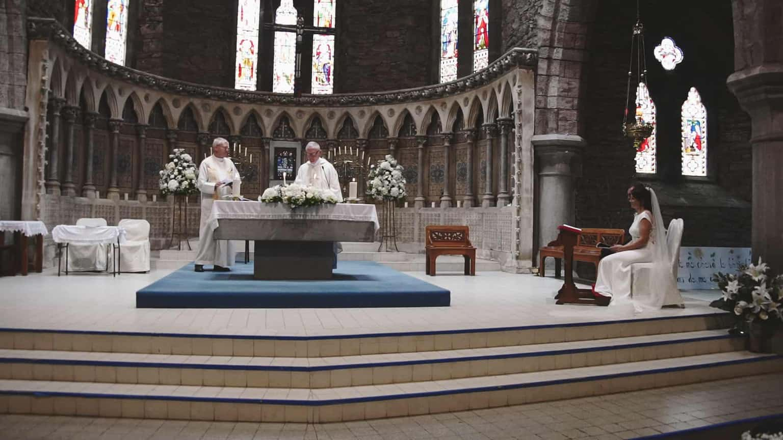 Priest at the altar looking down.