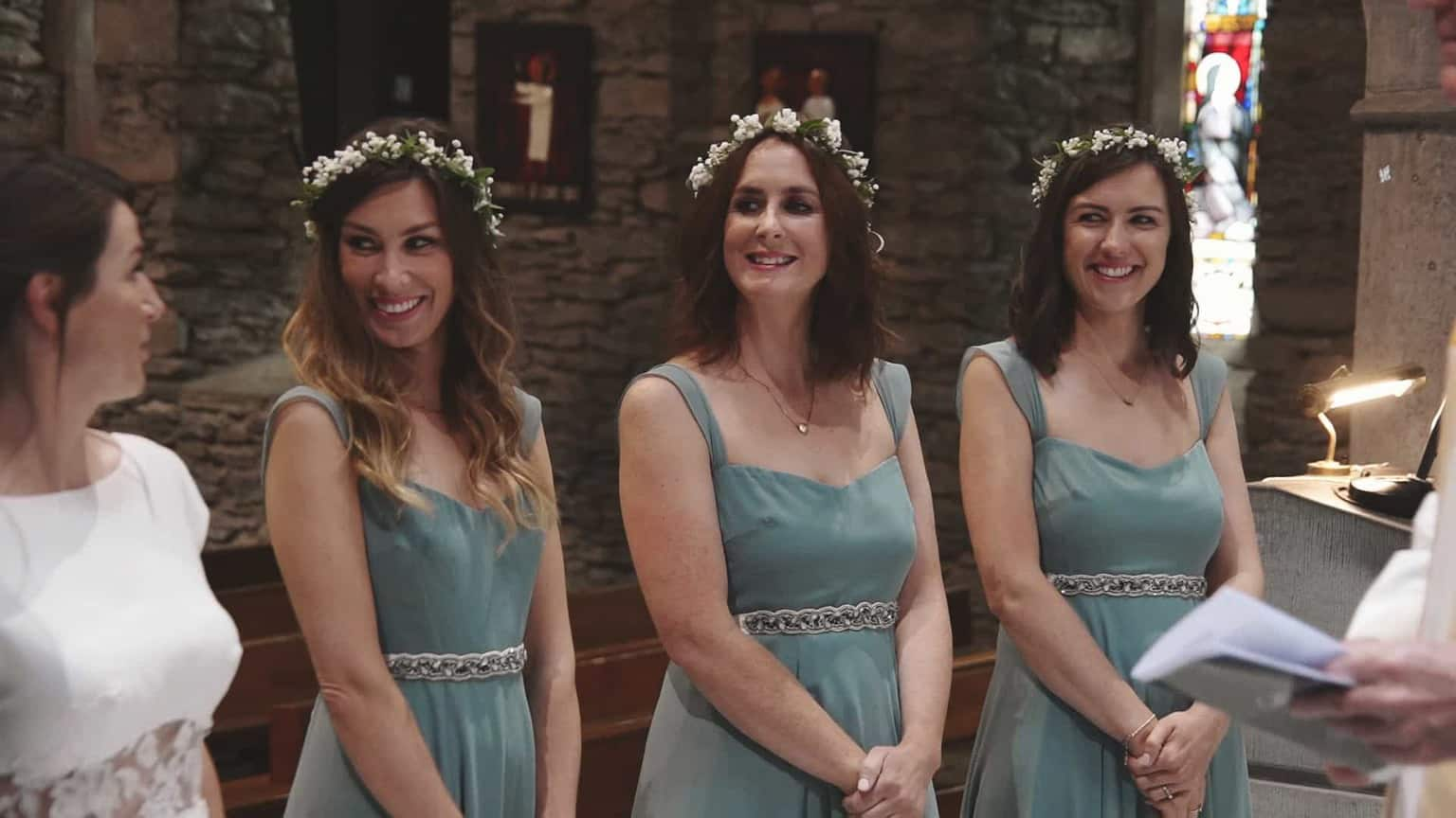 Bridesmaid are smiling during vows.