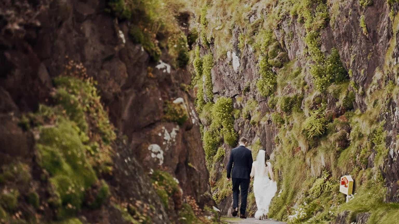wedding couple walking between rocks.