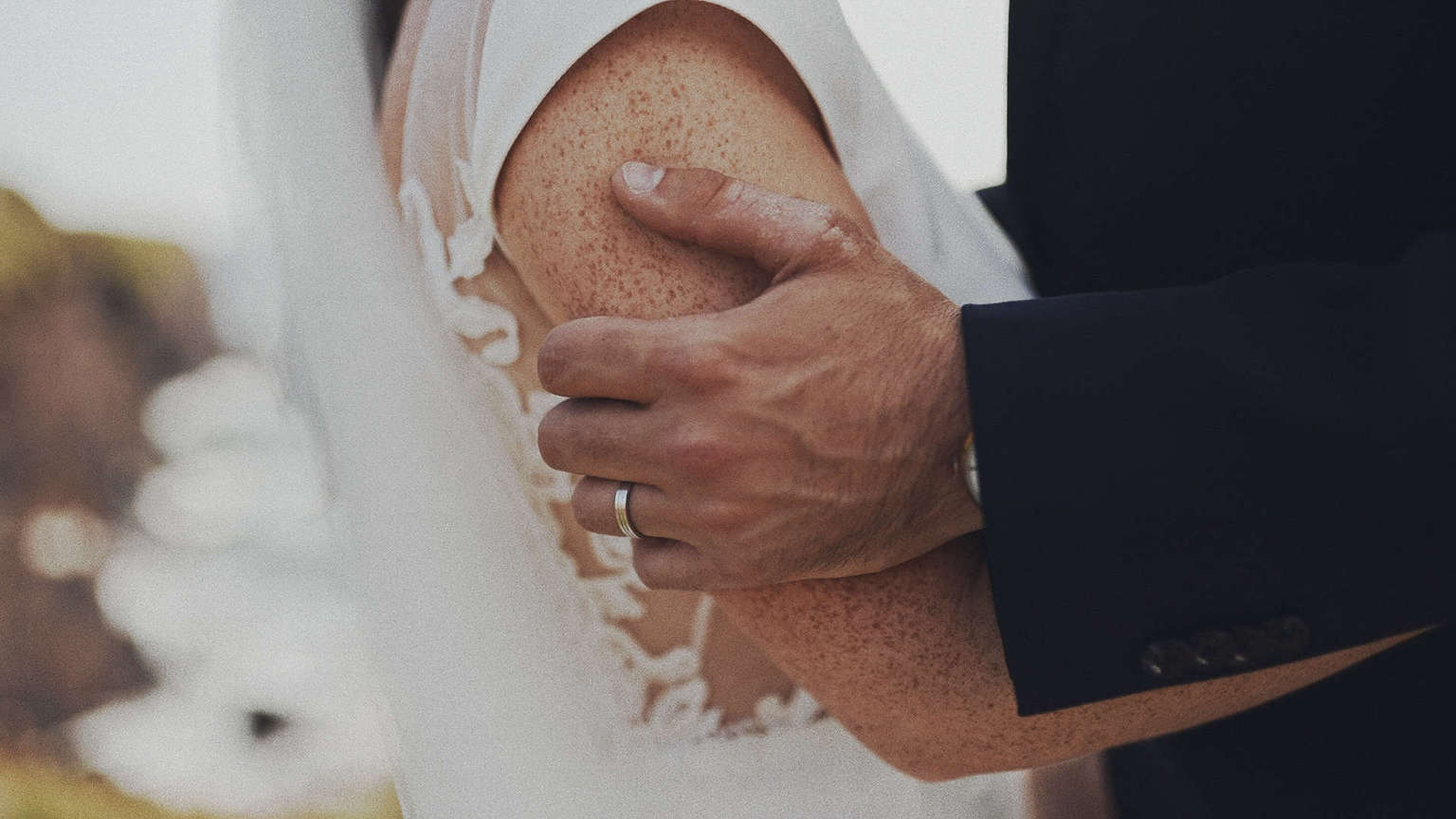 Groom is holing tightly brides arm