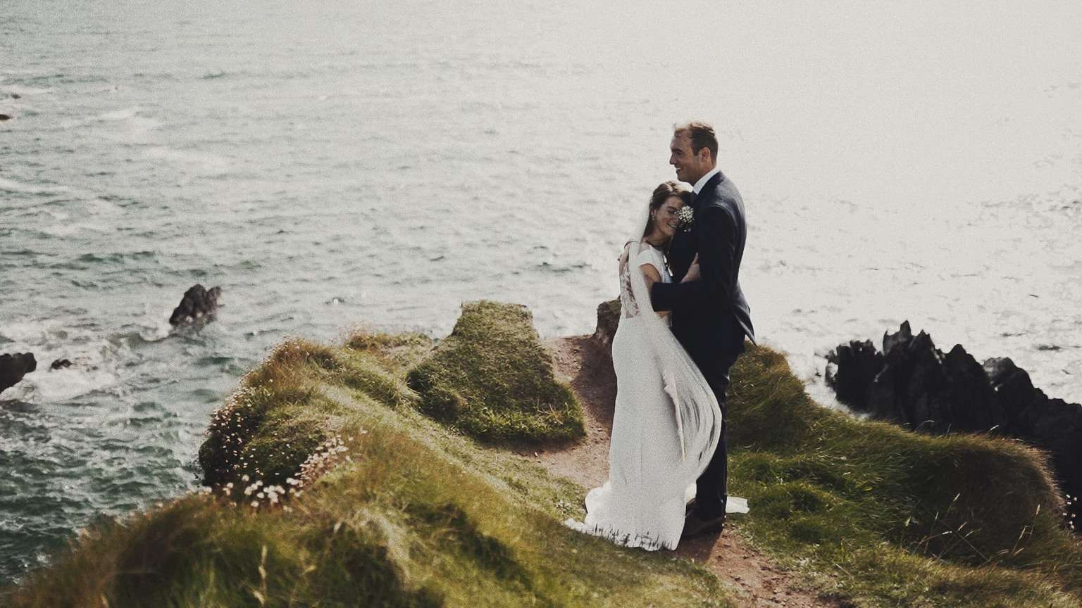 Bride and Groom standing on cliffs