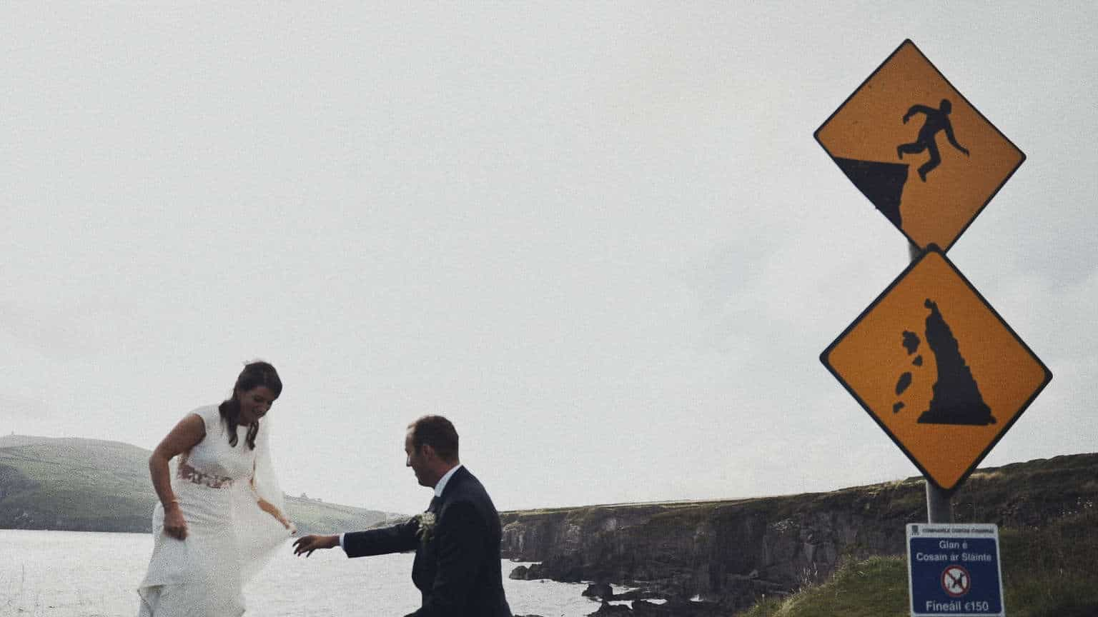 Bride and groom coming down from danger cliffs during wedding photo .