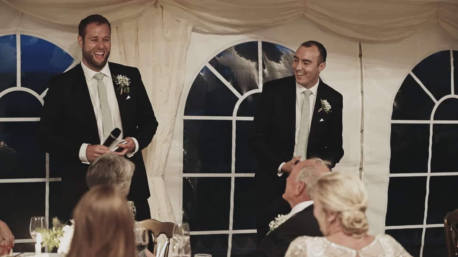 Two best men entertaining wedding crowd.