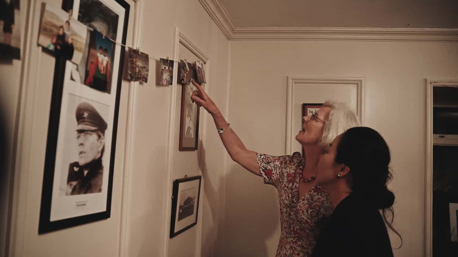 Ladies admiring pictures on the wall.