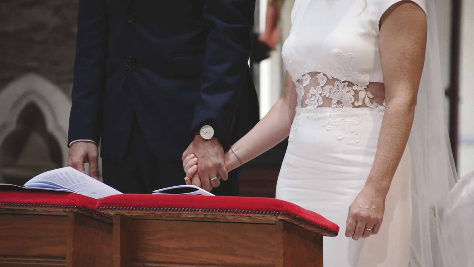 newly couple holding hands in church.
