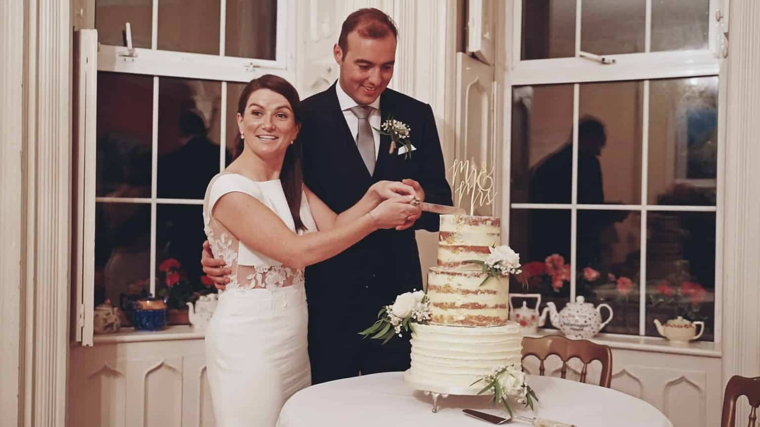 Bride and groom are cutting wedding cake.