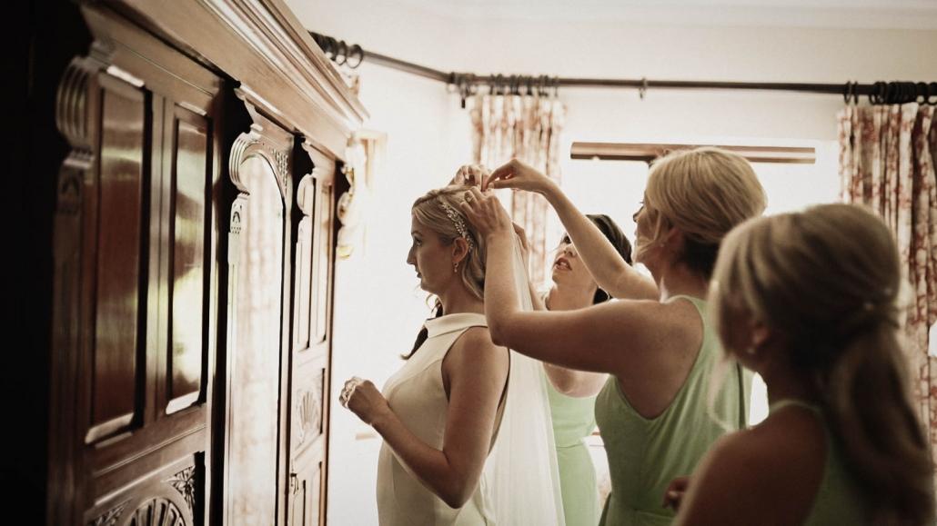 bridesmaids putting wedding veil