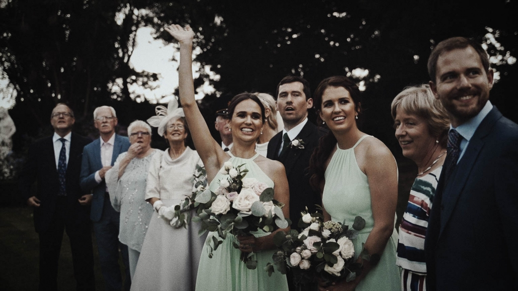 bridesmaid holding bouquet and waving to take picture