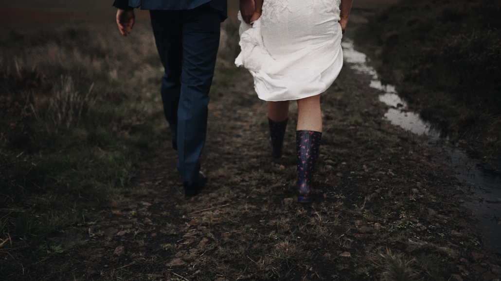 Bride wearing wellingtons and walk with groom.