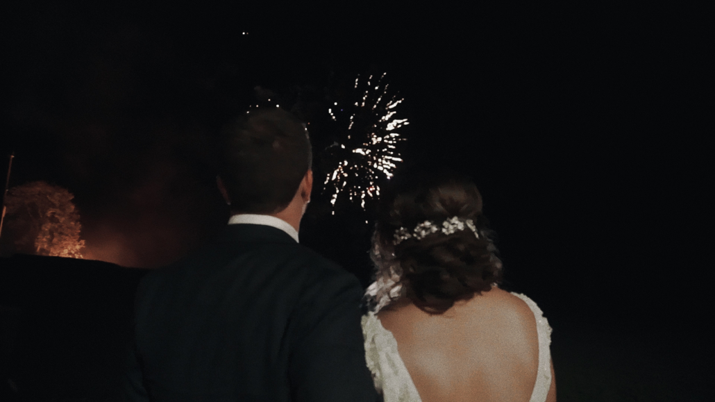 Bride with groom are admiring fire works.