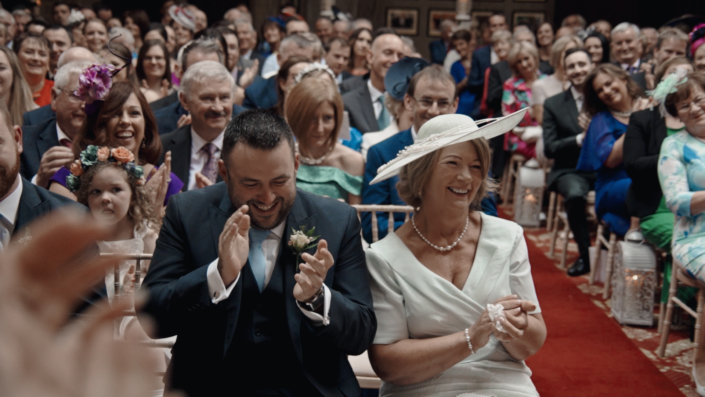Mother clapping to wedding kiss.