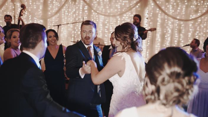 Bride wit groom enjoying first dance.