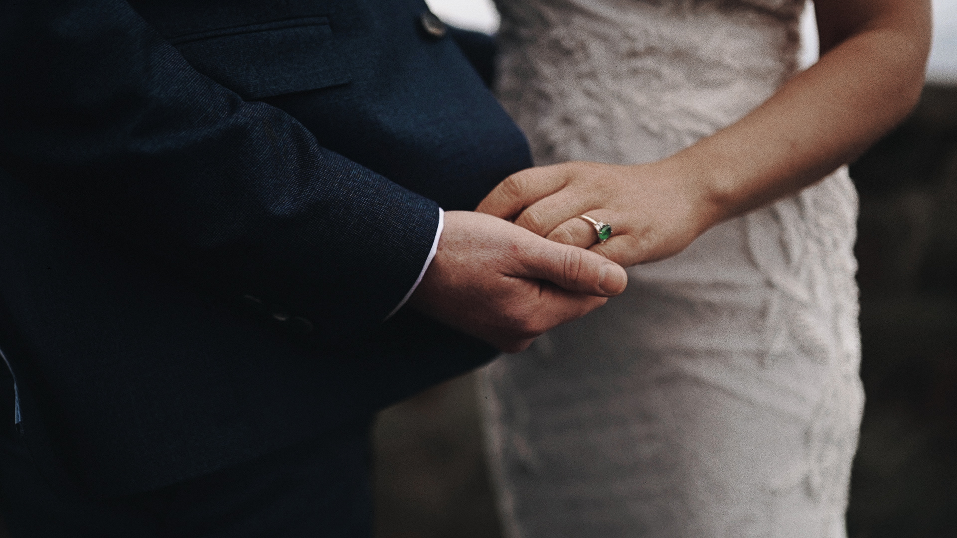 Newly couple holding hands with wedding rings.