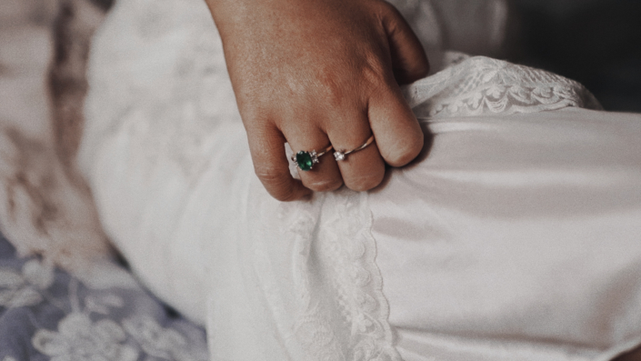 emerald engagement ring on bride hand