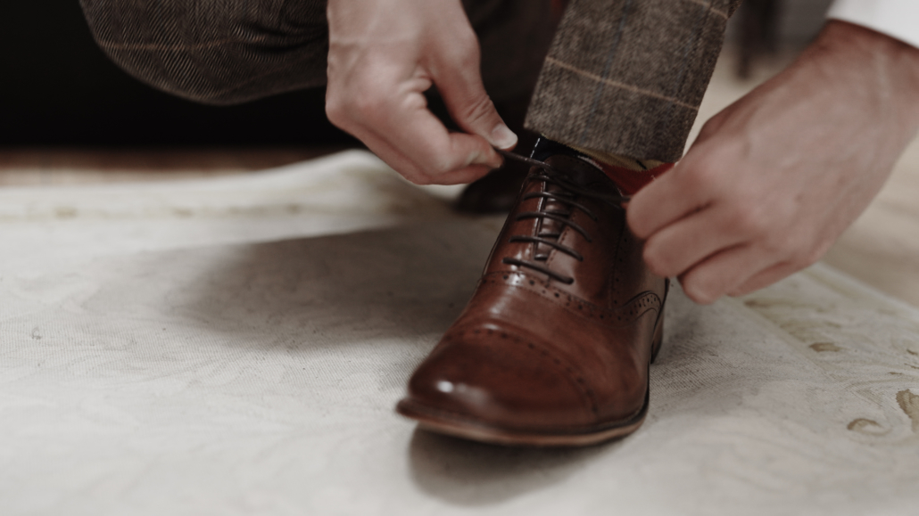 groom is tiding shoes